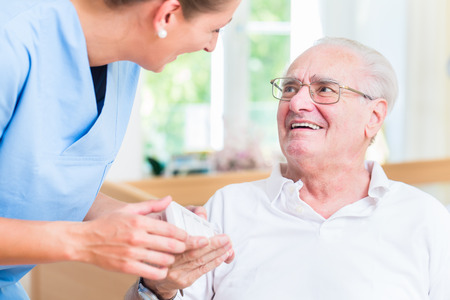 social care: Nurse giving senior man prescription drugs