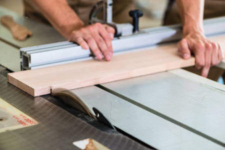 cabinet maker: Carpenter cutting wooden board with circular saw