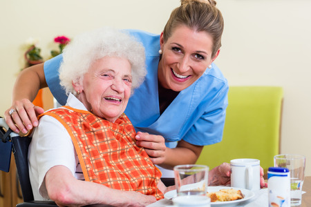 Nurse with senior woman helping with meal Stockfoto