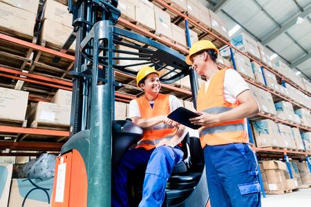 I lavoratori in logistica di magazzino a lista di controllo carrelli elevatori Archivio Fotografico