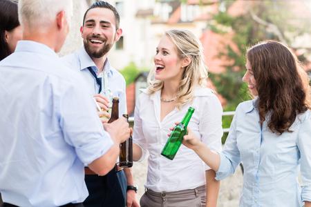 Büro-Kollegen trinken Bier nach der Arbeit auf der Terrasse feiern Standard-Bild - 51756044