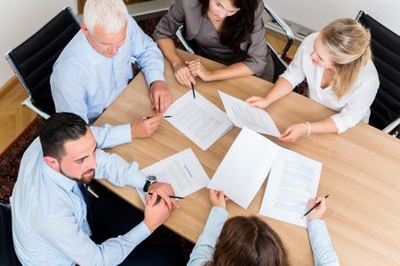 negociacion: Los abogados que tienen reunión del equipo en la lectura de documentos bufete de abogados y acuerdos de negociación