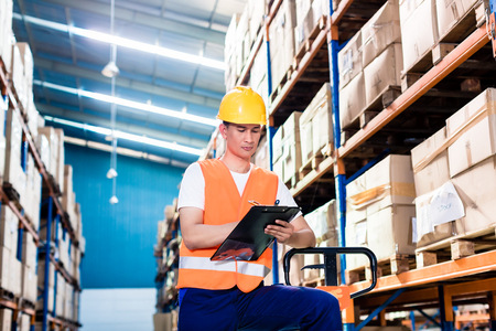 pallet truck: Asian man in industrial warehouse checking list