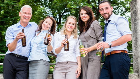 beer after work: Office colleagues drinking beer after work on terrace celebrating