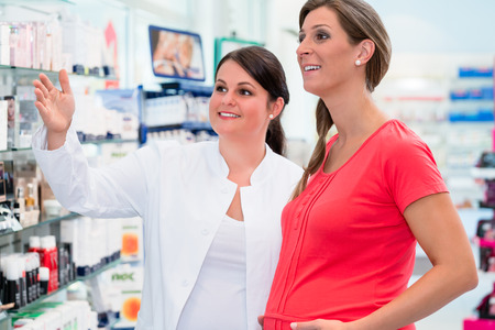 Pharmacist showing pregnant woman drugs in pharmacy or drug store, both women are standing in front of a shelf