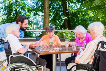 Skupina seniorů a sestra hrací karty v domově