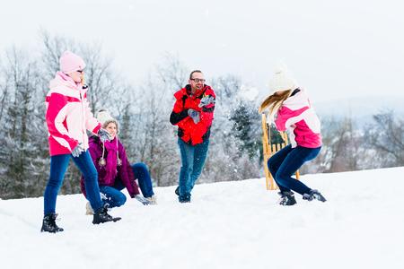 boule de neige: Famille avec des enfants ayant bataille de neige en hiver Banque d'images
