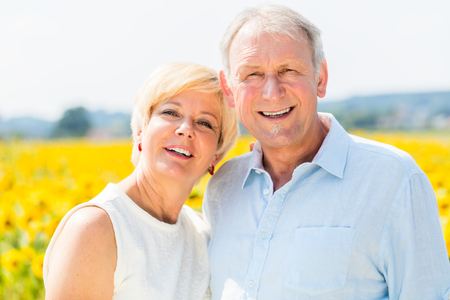 couples hug: Woman and man, seniors, standing at sunflower field