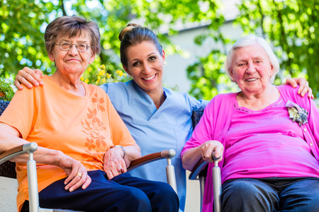 Geriatrica infermiere Rossa chiacchierata con donne maggiori