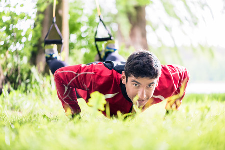 pushup: Man doing fitness push-up with sling Stock Photo