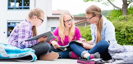 satchel: Students doing homework for school together reading in their books Stock Photo