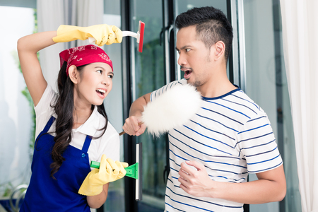 staging: Asian woman and man having fun cleaning home staging a mock fight with chores utensils