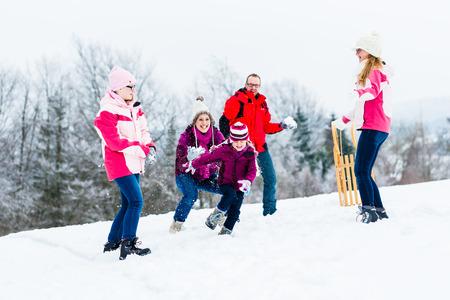 palle di neve: Famiglia con bambini che hanno battaglia a palle di neve in inverno
