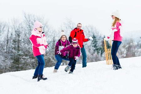 girl fight: Family with kids having snowball fight in winter