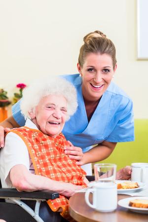年配の女性が食事を手伝うことと看護師します。 写真素材