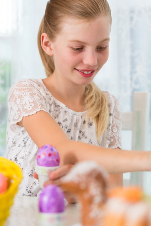 paschal lamb: Girl is coloring Easter eggs by painting on them Stock Photo
