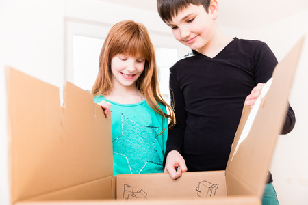 family moving house: Children unpacking boxes in new home