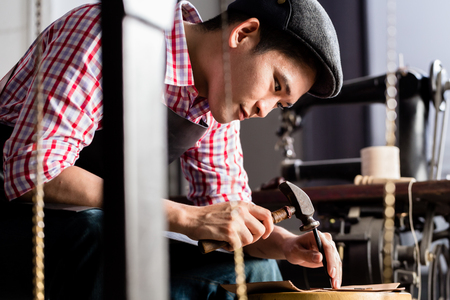 saddler: Asian shoe or belt maker in his leather workshop with sawing machine in background