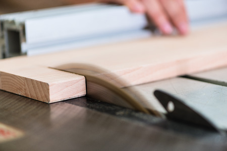 carpentry: Carpenter cutting wooden board with circular saw