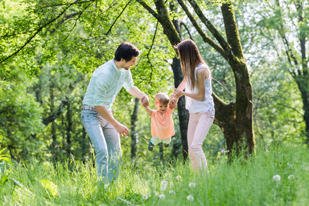 letting: Family having walk together in summer holding hands and letting the little boy fly