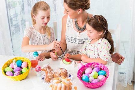 huevos de pascua: Familia con la madre y los niños para colorear los huevos de Pascua