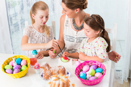 paschal lamb: Family with mother and kids coloring Easter eggs
