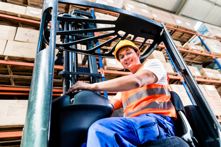 forklift driver: Forklift driver in industrial logistics warehouse looking at the camera Stock Photo