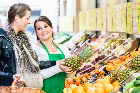 saleslady: Woman buying groceries at farmers market stand. saleswoman helping her choose