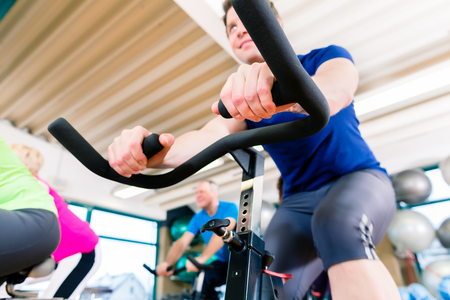 man gym: Man at Fitness Spinning on bike in gym, shot from a low angle Stock Photo