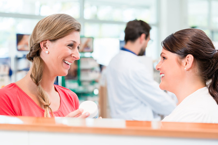 advised: Customer shopping in pharmacy or drug store being advised by sales lady on what cosmetics or products to buy