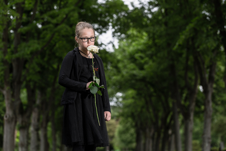 graves: girl with white rose mourning deceased on graveyard being an orphan now Stock Photo