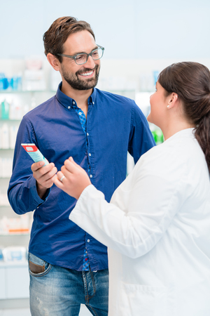 drug store: Pharmacist talking to customer in drug store, woman and man standing in front of shelves Stock Photo