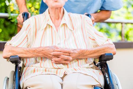 wheel chair: Geriatric nurse pushing senior lady in wheel chair thru home