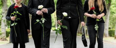 Torso van de familie op begraafplaats rouw die rode en witte rozen in handen