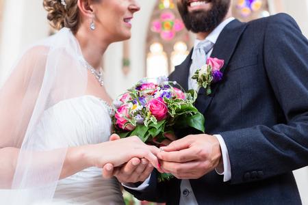 heirat: Groom Rutschring am Finger der Braut bei der Hochzeit Lizenzfreie Bilder
