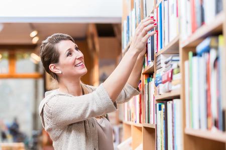 choosing: Woman choosing book in bookstore
