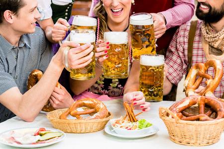 Im Biergarten - Freunde in Tracht, Dirndl und Lederhosen trinken ein frisches Bier in Bayern, München, Deutschland