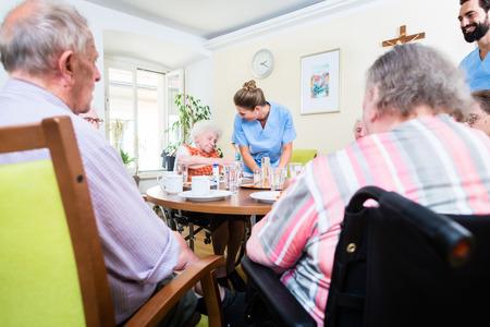 Grupo de personas mayores que tienen los alimentos en el hogar de ancianos, una enfermera está cumpliendo Foto de archivo