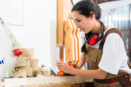 cabinet maker: Carpenter woman working with planer in her workshop