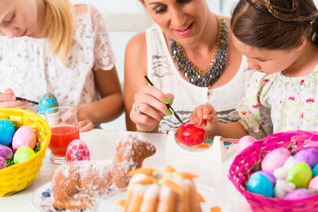 Family with mother and kids coloring Easter eggs