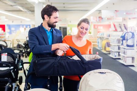 妊娠中の女性、ベビーカーを買って赤ちゃんお店のカップル 写真素材
