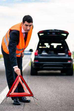 warning vest: Man with car breakdown erecting warning triangle on road