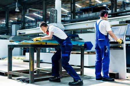 Arbeider team in de fabriek bespreken in de voorkant van de machine