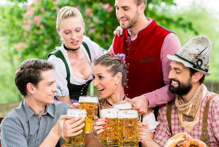 tracht: In Beer garden - friends in Tracht, Dirndl and Lederhosen drinking a fresh beer in Bavaria, Munich, Germany