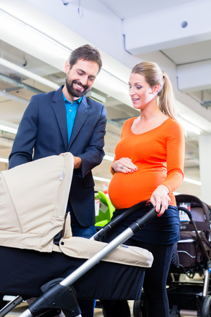 shopping buggy: Couple in baby shop buying stroller, the woman in pregnant Stock Photo