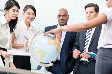 Les gens d'affaires en réunion sur la Stratégie discuter de nouveaux marchés regardant un globe