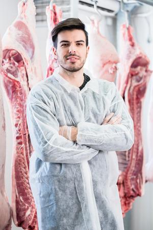 carne cruda: Trabajador en la carnicería de pie delante de las canales y listas para el procesamiento de carne Foto de archivo