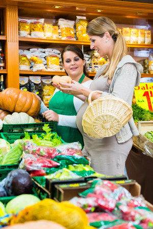 saleslady: Woman buying pumpkin and vegetables in delicatessen
