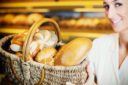 salesgirl: Baker woman in backer selling bread in basket, filtered image Stock Photo