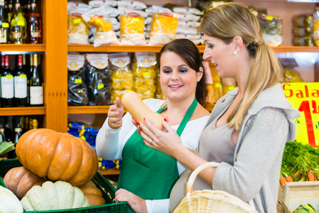 saleslady: Woman buying pumpkin and vegetables in delicatessen